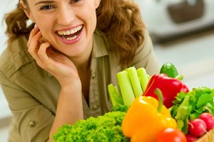 Happy young housewife near plate full of vegetables in modern ki