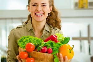 Happy young housewife holding plate full of vegetables in modern