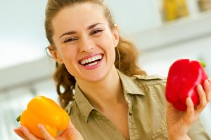 Happy young housewife holding red and yellow bell peppers