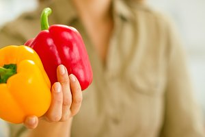 Closeup on fresh bell peppers in hand of young woman
