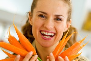 Smiling young woman showing fresh carrots