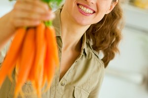 Happy young housewife giving bunch of carrots