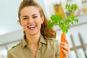 Smiling young housewife holding carrot in kitchen