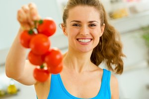 Happy young woman holding bunch of tomato in kitchen