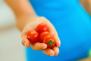 Closeup on cherry tomato in hand of woman