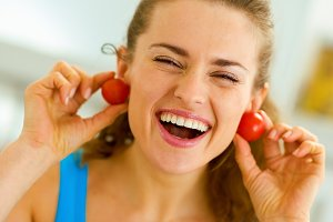 Smiling young woman using cherry tomato as earrings