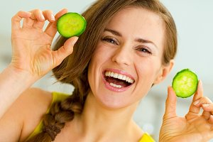 Smiling young woman showing slices of cucumber