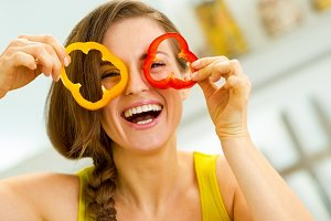 Funny young woman showing slices of bell pepper