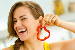 Happy young woman using slice of bell pepper as earring