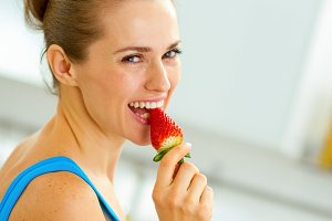 happy young woman eating strawberry