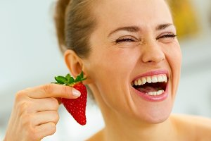 Laughing young woman using strawberry as earring