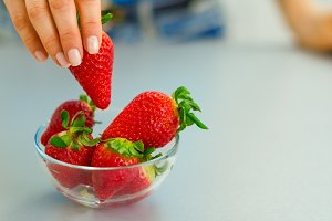 Closeup on young woman taking strawberry