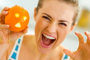 Young woman scaring with orange with hallowing face
