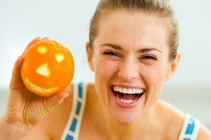 happy young woman showing halloween orange