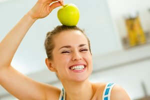 happy young woman holding apple on head
