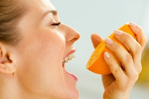 Young woman pressing orange juice in mouth