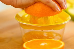 Closeup on woman making orange juice