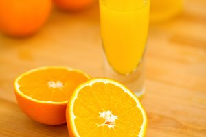 Closeup on glass of orange juice and oranges on cutting board
