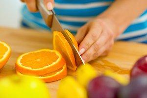 Closeup on young woman cutting orange