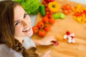 Happy young housewife cutting fresh vegetables