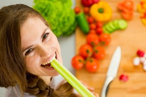 Happy young woman eating celery in modern kitchen