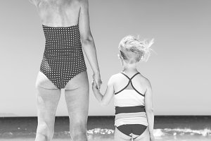 young mother and child on seashore looking into distance