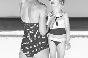 happy modern mother and child on beach applying sun screen