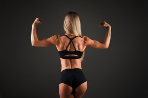 Strong Athletic woman Fitness Model posing back muscles, triceps, latissimus over black background