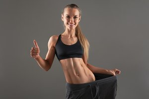 Full-length portrait of attractive slim young smiling woman in big pants showing successful weight loss with her thumb up, isolated on gray background