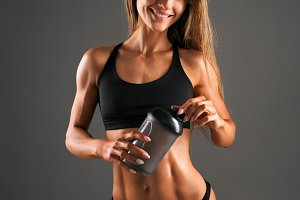 Resting time. Sporty girl drink water. Photo of muscular fitness model on black background. Health concept.