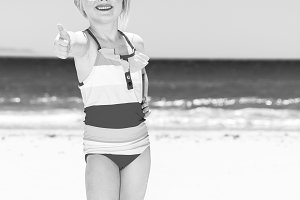 happy modern girl on beach showing thumbs up