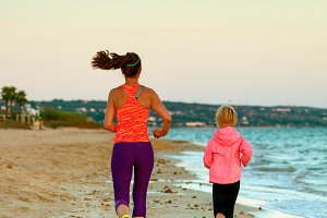 fit mother and daughter on beach in evening running