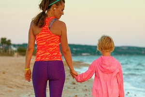 young mother and daughter on seashore in evening walking