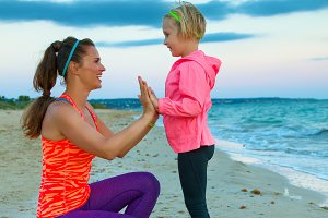mother in sport style clothes  giving child high five on beach