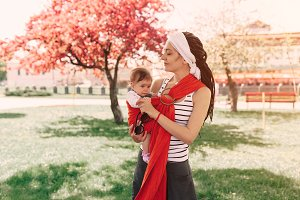 Mother carry a infant baby in wrap sling in park. Springtime. Concept of natural parenting