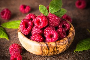 Fresh raspberries in wooden bowl.