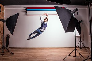Portrait of a young hipster man in a studio, jumping. Copy space.