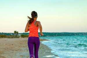 healthy woman jogger on seashore in evening running