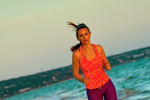 healthy fit woman on seashore in evening running