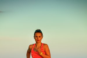 fit woman on seacoast in evening jogging