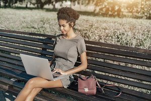 Black girl with laptop on park bench