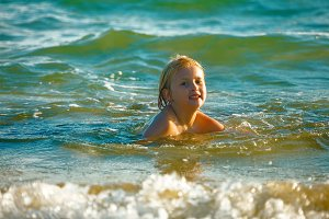 portrait of happy blond child bathing in sea
