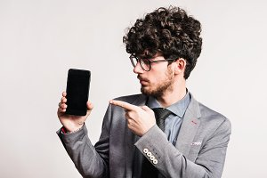 Portrait of a young man with a smartphone in a studio. Copy space.