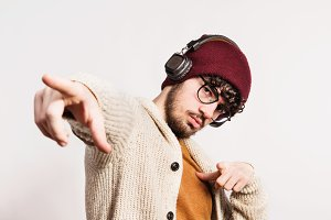 Portrait of a young man with hat and headphones in a studio.