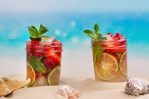 Strawberry mojito on summer sandy beach