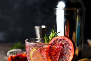 Blood Orange Margarita coctail with ice and thyme on dark backgorund