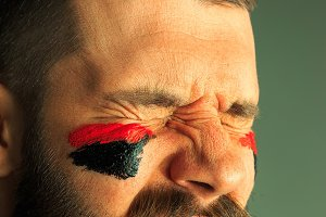 Portrait of a man with the flag of the Germany painted on him face.