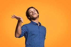 Beautiful male half-length portrait isolated on orange studio backgroud. The young emotional surprised man