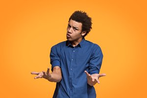 Beautiful male half-length portrait isolated on orange studio backgroud. The young emotional afro man
