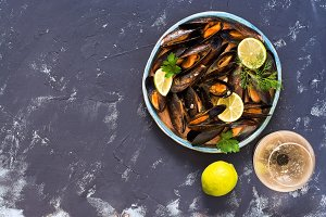 Mussels in a wine sauce on a gray background, a glass of wine, lime. Top view, copy space.